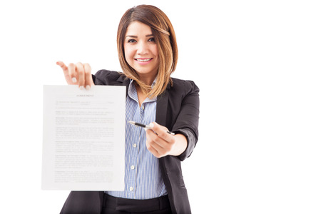 requesting: Attractive young female executive handing over a contract and requesting a signature on a white background