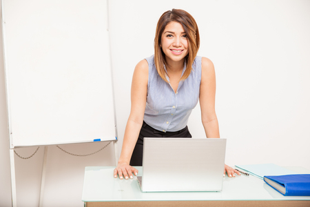 Cute young woman leaning on a desk with a laptop computer and standing next to a flip chart Фото со стока