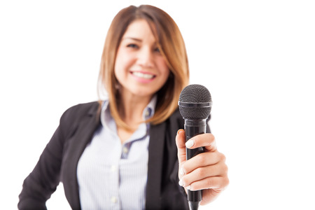Happy female presenter in a suit handing over the microphone. Focus on microphone