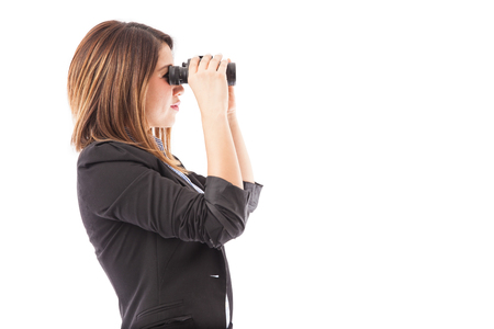 looking ahead: Profile view of a businesswoman looking through binoculars representing a job search. Plenty of copy space
