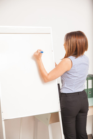 rear view: Rear view of a young female teacher writing on a flip chart and giving a class