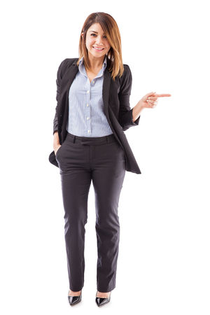 woman pointing: Full length portrait of a beautiful young salesperson pointing right towards copy space and smiling