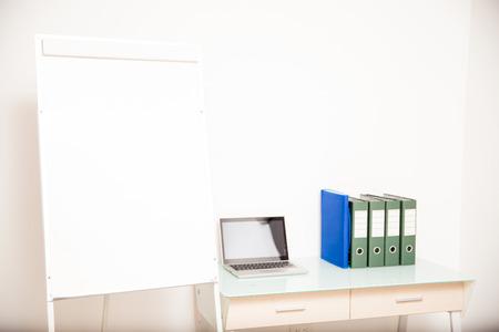 Bureau d'un enseignant avec un ordinateur portable, des documents et un tableau blanc avec beaucoup d'espace de copie