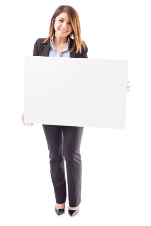 sales executive: Full length view of a gorgeous young Hispanic businesswoman holding a big sign against a white background and smiling Stock Photo