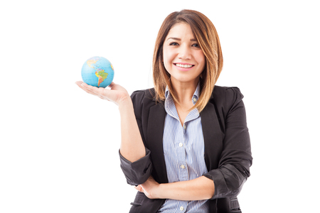 hispanic woman: Gorgeous Hispanic young woman in a suit holding a small globe and showing that hers in a global company