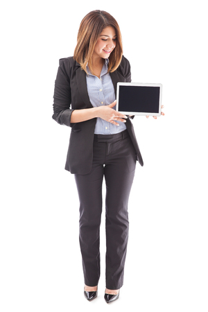 full lenght: Full lenght portrait of a beautiful sales executive holding a tablet computer and looking at the screen