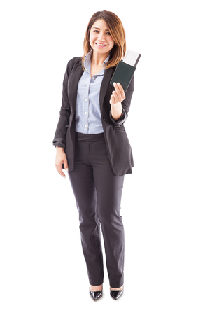 sales executive: Full length view of a female sales executive of an airline holding a boarding pass and a passport on a white background Stock Photo