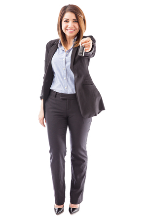 handing over: Full length view of a female sales executive of a car dealership handing over the keys to a new car