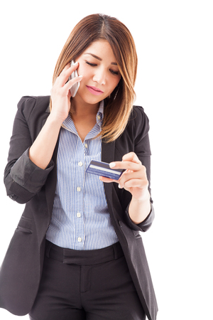activate: Good looking young woman in a suit calling customer service at her bank to activate her new credit card