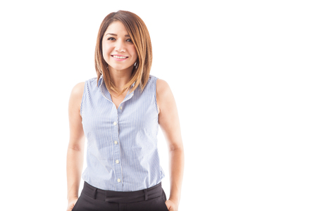 Beautiful young Hispanic teacher smiling against a white background
