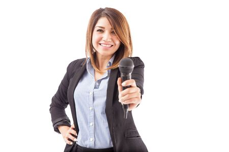 handing over: Attractive young woman in a suit handing over a microphone to talk, on a white background