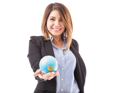 Portret van een leuk en gelukkig vrouwelijke reisbureau met een kleine wereldbol in haar hand en glimlachend
