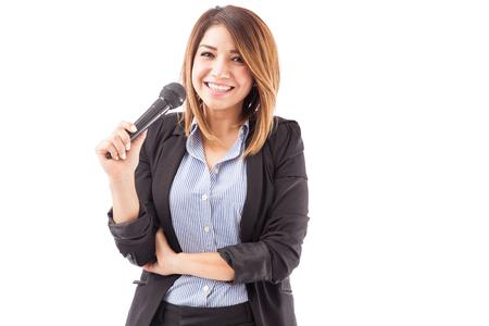 exhibitor: Retrato de una joven empresaria hispana sosteniendo un micrófono durante un seminario y sonriente