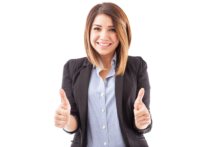two thumbs up: Portrait of a gorgeous young Hispanic female executive holding out two thumbs up and smiling