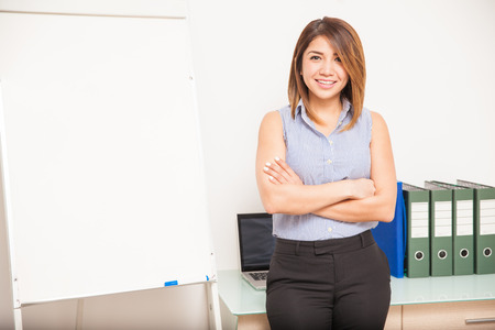 flip chart: Attractive young businesswoman ready to give a business presentation and standing next to a flip chart