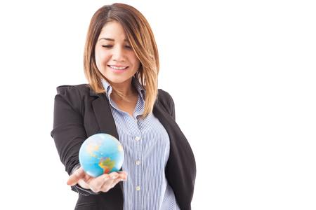 Mooie en succesvolle zakenvrouw met een wereldbol die aangeeft dat de hare is een internationale business Stockfoto