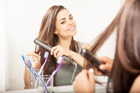 flat iron: Pretty young brunette straightening her hair in the bathroom using a flat iron and smiling