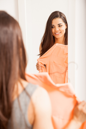 woman closet: Beautiful young brunette trying some clothes in front of a mirror in a clothing store Stock Photo