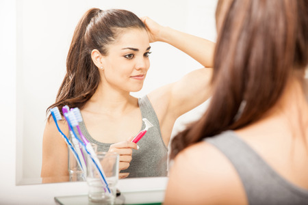 Portrait of a beautiful Hispanic young woman lifting looking at her armpits in a mirror after shaving them with a razor
