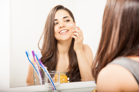 Giovane e bella donna sempre pronto nel bagno e l'applicazione di una crema sul viso