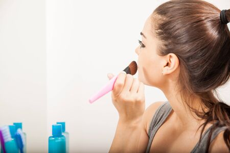 putting on: Profile view of a young brunette putting some blush on her face in front of a mirror in the bathroom