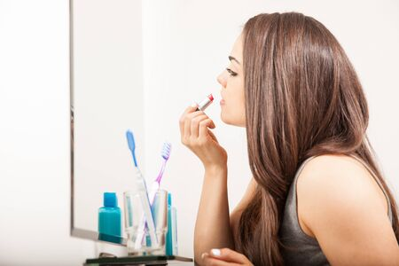 putting on: Profile view of a cute young woman putting some lipstick on and getting ready to go out on a date