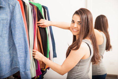 woman closet: Pretty Hispanic young woman standing in a dressing room and deciding what to wear