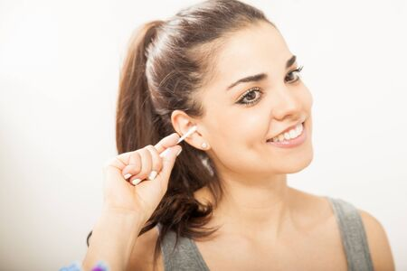 swab: Closeup of a pretty young woman cleaning her ears in the bathroom with a cotton swab and smiling