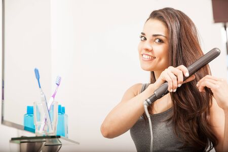 Beautiful young Hispanic woman using a flat iron to straighten her hair in the bathroom