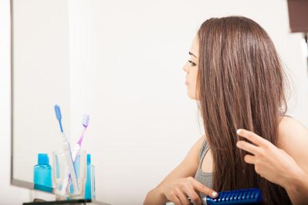 Voir le profil d'une jeune femme mignonne brosser ses cheveux bruns devant un miroir de salle de bain