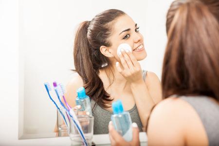 Gelukkig jonge Spaanse brunette met behulp van make-up remover met een wattenschijfje in de badkamer