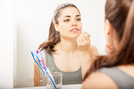 putting on: Gorgeous young Latin woman putting some lipstick on in front of a mirror in the bathroom