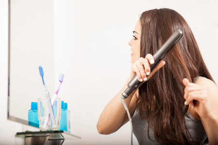 flat iron: Profile view of a pretty young brunette using a flat iron to style and straighten her hair in front of a mirror Stock Photo