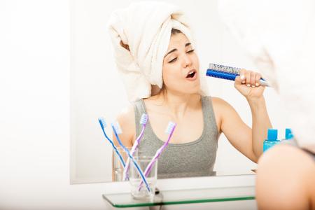 mujer bañandose: Bastante joven divirtiéndose y cantando a un cepillo para el cabello después de tomar una ducha Foto de archivo