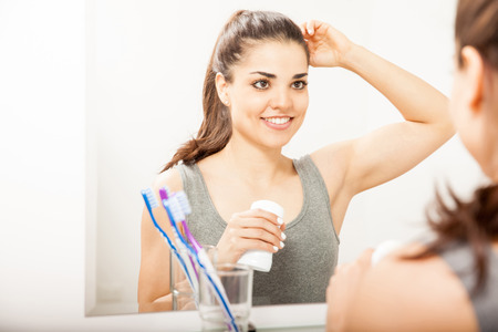 Attractive Hispanic young woman putting on deodorant while looking at herself in a mirror in the bathroom Stock Photo