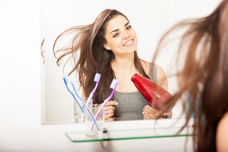 Porträt einer schönen jungen hispanischen Frau, die ihr Haar mit einem Fön im Badezimmer trocknen
