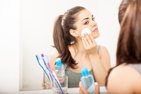 Retrato de una hermosa morena joven con una almohadilla de algodón para quitar su maquillaje en el baño por la noche