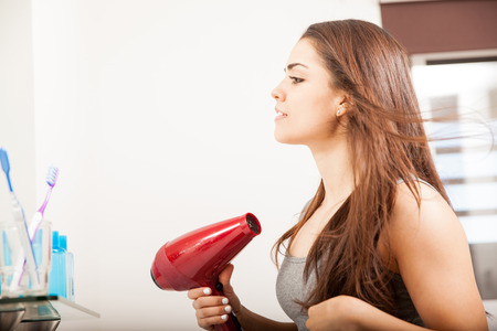blow dryer: Profile view of a cute young woman using a blow dryer and drying her hair in a bathroom Stock Photo