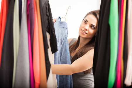 woman closet: Attractive young woman sorting through her clothes inside a closet at home
