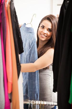 vistiendose: Retrato de una mujer joven y bonita América tratando de encontrar algo que ponerse en su armario en su casa