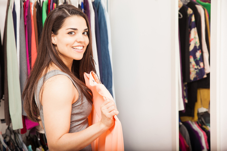 getting dressed: Portrait of a gorgeous young Hispanic woman getting dressed in front of a mirror in a dressing room and smiling