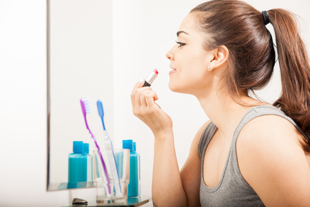 putting on: Profile view of a beautiful young woman putting some lipstick on in front of a mirror in the bathroom