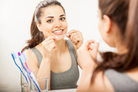 whitening: Portrait of a happy Hispanic young woman using a whitening strip on her teeth and smiling Stock Photo