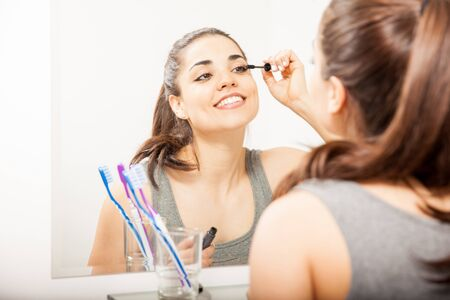 'getting ready': Portrait of a young woman getting ready in the bathroom and putting on some mascara in front of a mirror Stock Photo