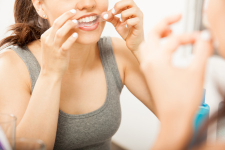Closeup of a cute brunette applying a whitening strip on her teeth in front of a mirror in the bathroom