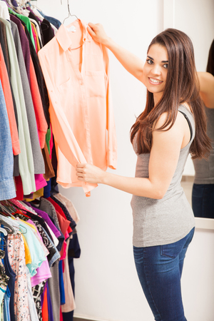 Portrait of a cute young woman holding a blouse while standing in front of a closet in a bedroom