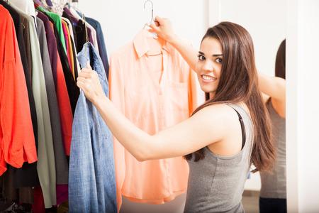 vistiendose: Retrato de una mujer joven linda que sostiene dos opciones de ropa para usar mientras vestirse en casa