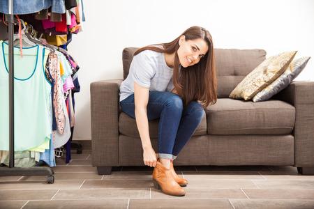 Portrait einer netten jungen hispanischen Frau immer gekleidet und Schuhe an in einer Umkleidekabine zu Hause setzen