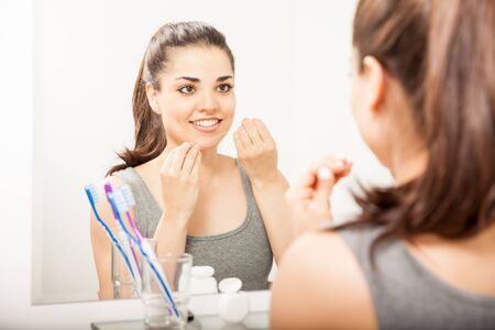 Portrait of a young woman standing in front of a mirror in the bathroom and cleaning her teeth with dental floss Stock Photo