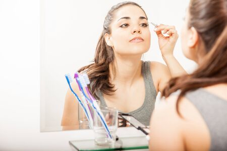 'getting ready': Beautiful young woman getting ready in the bathroom and putting on some makeup on her eyes Stock Photo